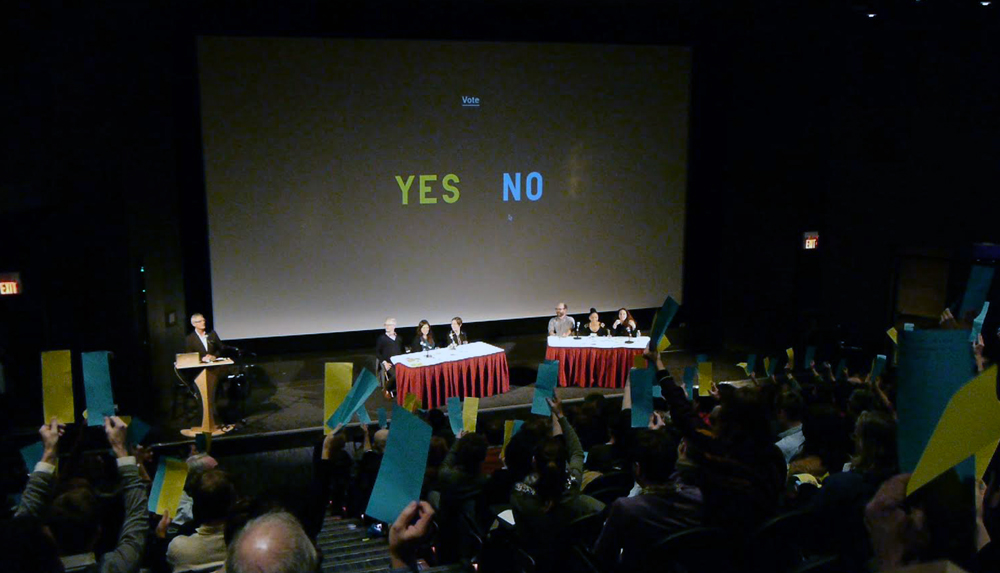 """Audience members vote at the Institutions By Artists keynote debate """"Should artists professionalize?"""" October 13, 2012."""