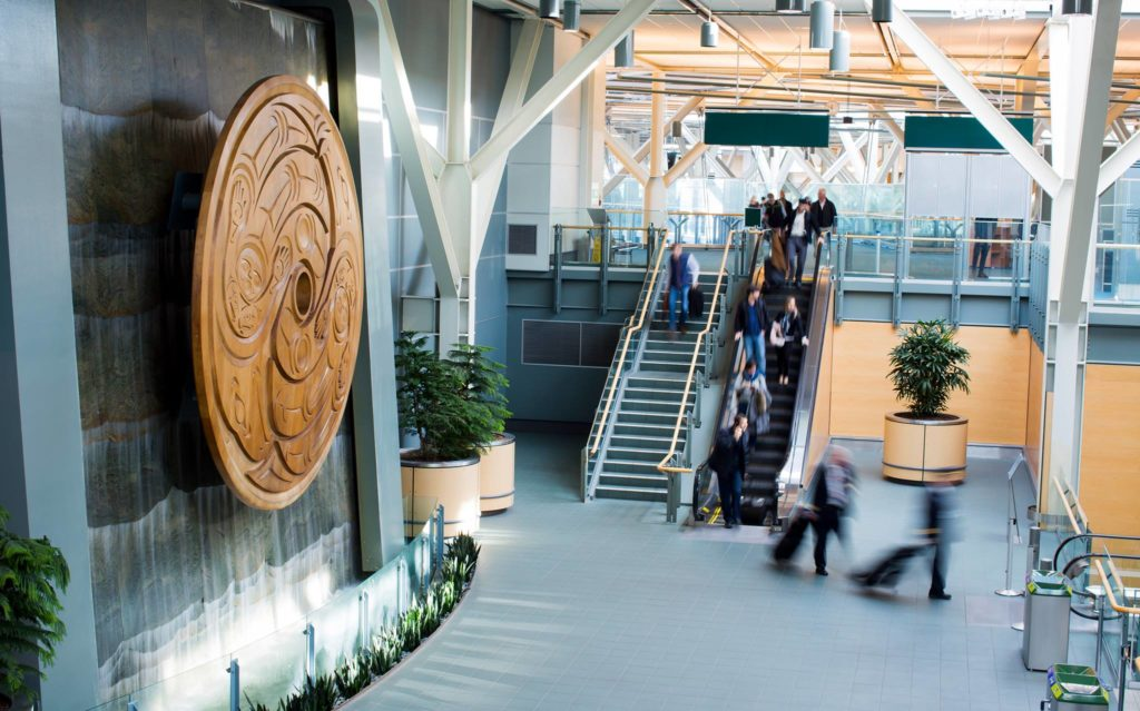 Susan Point's <em>Flight</em>, at left, is the world's largest Coast Salish spindle whorl and is permanently installed at the Vancouver Airport. Photo: Vancouver Airport Facebook page.